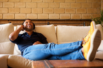 Cheerful young black man lying on sofa with headphones and listening to music
