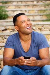 Young african man sitting outside using smart phone and looking up