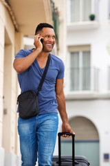 Handsome young man talking on mobile phone with bag
