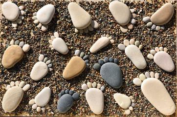 Pebble stones arranged like footprints on the beach