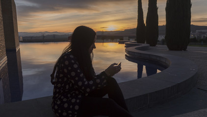 Woman with her mobile in the sunrise