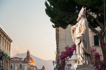 Statue outside the Church of St. Agatha in Catania, Sicily, with the town and Mount Etna in the background