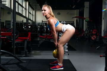 Fitness young sweaty girl with a sports body in a gym doing exercises with a weight