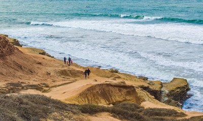 people walking on cliffs along pacific ocean at Point Loma San Diego