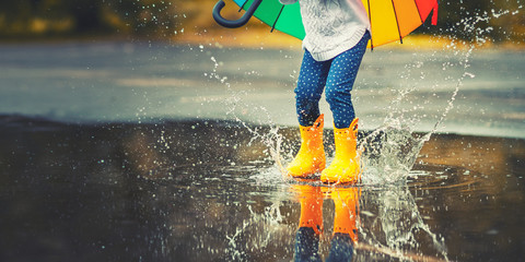 Feet of  child in yellow rubber boots jumping over  puddle in rain Wall mural