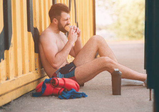 Man eats a hamburger after a workout. Very hungry, fatty and unhealthy food
