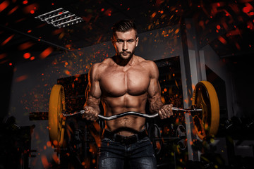 Fire and flame design. man in gym. Muscular bodybuilder guy doing exercises with barbell. Strong person. Sports background. Young athlete ready for weight lifting training