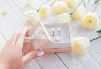 Woman opens a gift box with jewellery