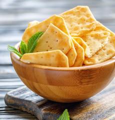 Crispy cracker with salt in a wooden bowl.