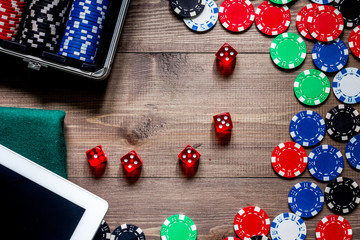 Compulsive gambling. Poker chips and the dice nearby tablet on wooden table top view copyspace