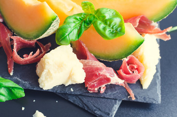 Concept of italian food with melon and prosciutto