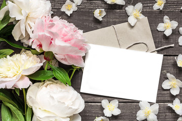 blank greeting card and envelope in frame of pink and white peonies and jasmine flowers