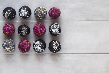 Various fitness bites, raw chocolate truffles, with rose petals, on gray background. Food photography, diet concept