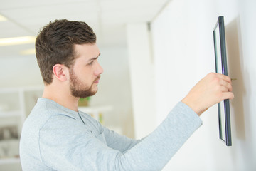 repairman putting picture frame onto wall