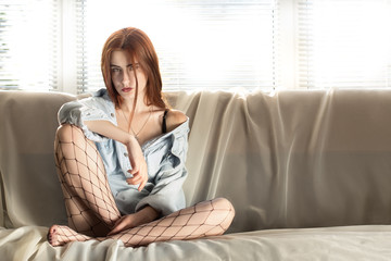 sensual beautiful woman sitting at sofa with blinds light in sunlight