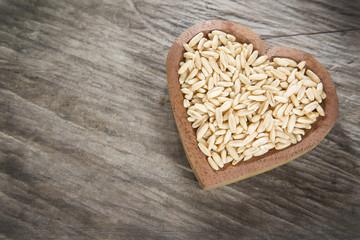Oat grains on wooden background - Avena sativa