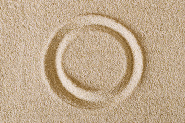 Circle shape imprint in sand surface. A closed curve, a ring or a disc in a rectangular flat sand area. Pictogram and sign. Macro photo close up from above.