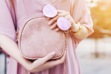 Elegant, trendy outfit. Pink color accessories. Fashionable woman posing in street. Model holding in hands small bag, sunglasses with reflection. Female fashion concept. Copy, empty space for text