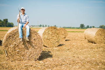 Smiling farmer sitting on an hay bale in his field