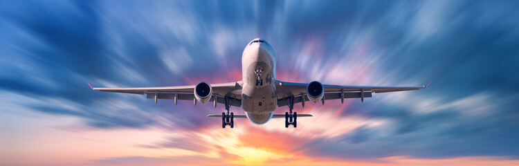 Airplane with motion blur effect. Landscape with passenger airplane is flying in the blue sky with blurred clouds at sunset. Travel background. Passenger airliner. Business trip. Commercial aircraft Wall mural
