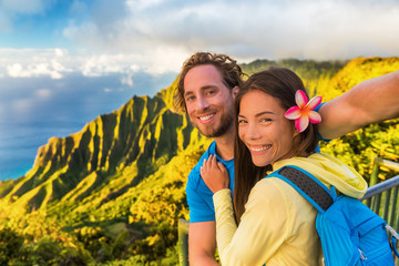 Wall Mural - Na pali hikers couple tourists taking selfie at Napali lookout in Kauai Hawaii. Travel friends taking smartphone picture at famous destination Kalalau hawaiian attraction.