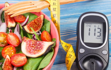 Fruit and vegetable salad and glucose meter with tape measure, diabetes, slimming and healthy nutrition concept