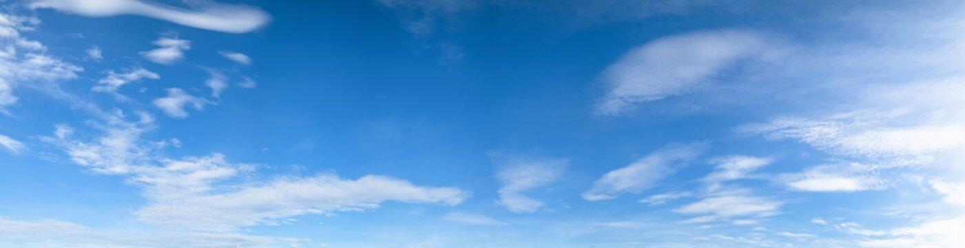 Panorama of blue sky background with white clouds on a sunny day