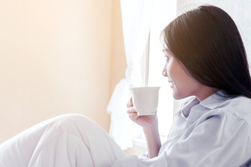 woman drinking coffee on bed