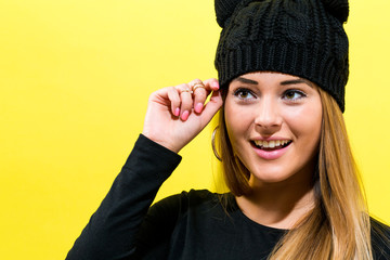 Girl wearing a cat knit hat on a yellow background