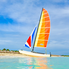Fototapete - The tropical beach of Varadero in Cuba with a colorful sailboat