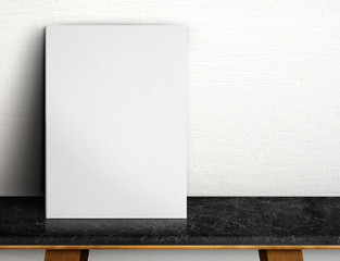 Blank White paper poster on black marble table at white concrete wall,Template mock up for adding your design and leave space beside frame for adding more text.