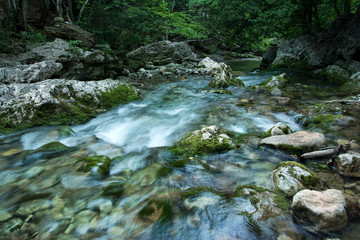 Forest creek with waterfalls. Water cascading over rocks.crystal clear water in mountain river.