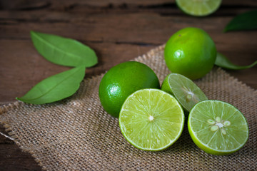 a Lime lemon with sack cloth on rustic wooden background.