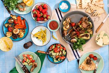 Dinner table with shish kebab, grilled vegetables, salad, snacks, strawberries