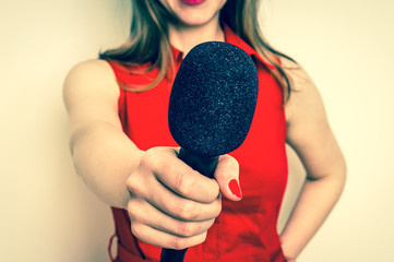 Female reporter with black microphone making interview