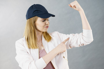 Young woman showing her arm muscles