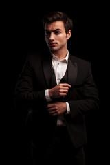elegant man in tuxedo and undone bowtie fixing his sleeve