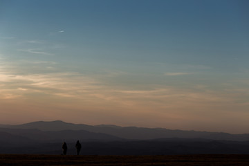 A boy and a girl on top of a mountain at sunset