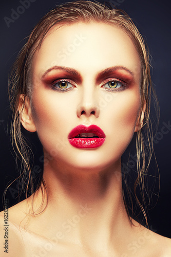 Beauty face of young woman, red lips makeup, clean skin and green eyes over dark background. Attractive Blonde wet hair lady. Youth and Skin Care Concept