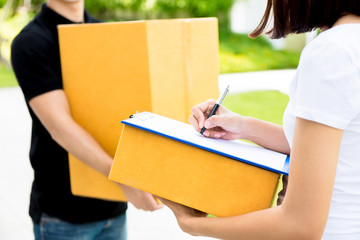 Woman signing document, receiving parcel box from delivery man