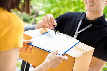 Delivery man pointing on the document showing where to sign, while delivering parcel box to a woman