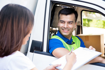 Delivery man in the car delivering package to a woman and giving her document to sign