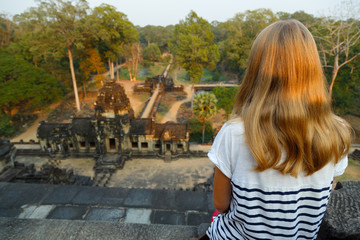 Young woman is sitting on the top temple and she is looking on panorama of Baphuon temple. Photographed in the temple complex of Angkor Wat, Cambodia