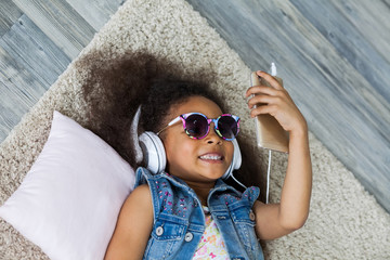 cute African girl at home, listening to music in big white headphones, Lies on the floor
