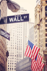 Wall Street and Broad Street signs with American flag in distance, shallow depth of field, color toning applied, New York City, USA.