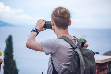 Man traveler with backpack makes a photo on your smartphone outdoors with mountains in the background