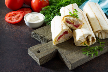 Shaurma lavash with fried chicken meat, fresh vegetables and creamy sauce on a background of brown stone. Copy space.