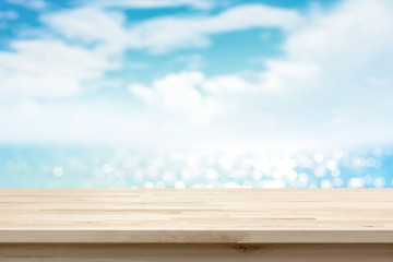 Wood table top on blur sparkling sea water and summer sky background