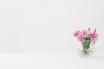 bouquet of pink Carnationflowers in vase on white table. Empty space for text