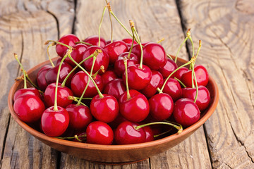Fresh cherry in bowl on wooden background.